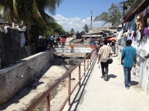 An urban system, just messy enough: a canal (left) doubles as a market corridor (right) in Ravine Pintade, Port-au-Prince, Haiti. Photo by the author.